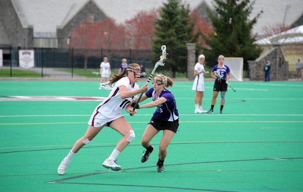 Courtney Miller '12 runs with the ball by a defender in a lacrosse game at Colgate.