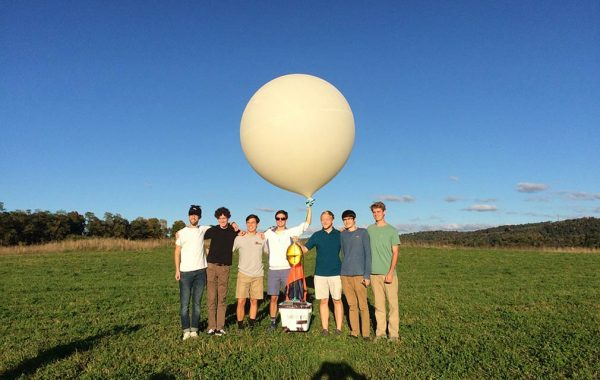 Seven students pose in a field with a weather balloon attached to a camera-housing apparatus