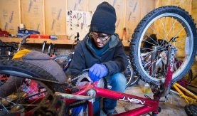 Student performs maintenance on the chain of an upturned bicycle