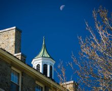 A daytime moon rises over McGregory Hall.