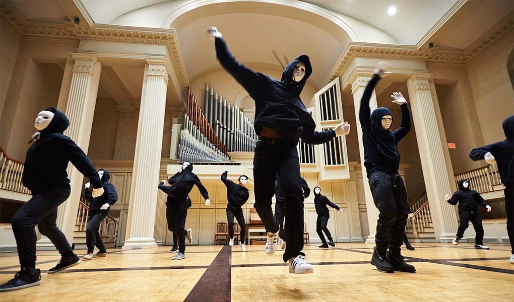 Student dancers dressed in black and wearing white masks on stage at Colgate Memorial Chapel.