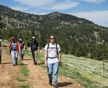 Students walk along a sunny Colorado trail