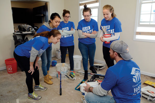 Colgate students huddle around for a lesson from a Habitat for Humanity volunteer