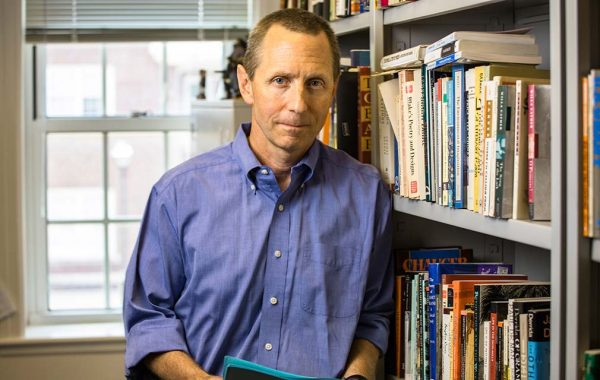 David Blake '85 leaning on a bookshelf
