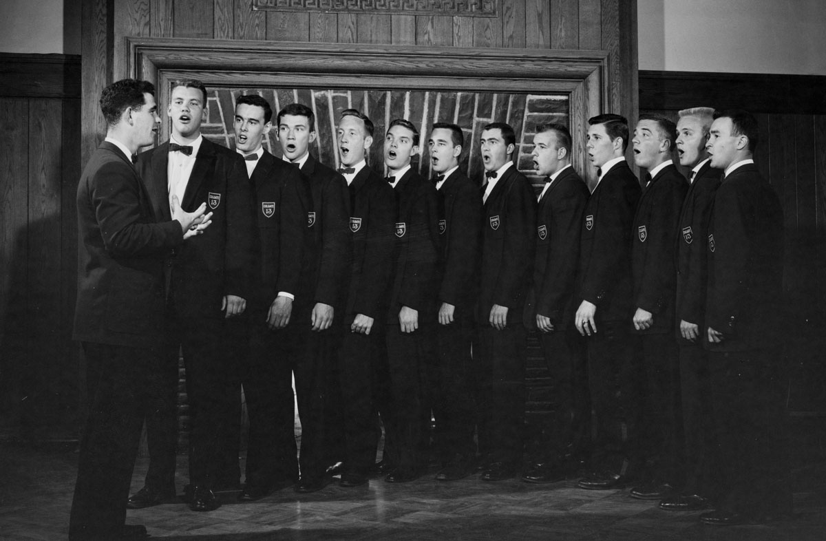 Archival photo of the Colgate 13 singing in the Hall of Presidents