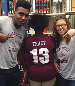 Library staff point to a student's 13 t-shirt