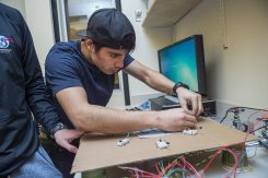 Anthony Castillo '19, an astrophysics major from Los Angeles, adjusts a switch on his Whack-A-Mole project