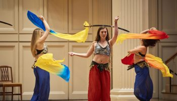 Students perform with the Bellydancing club at Dancefest, as two students twirl with scarves, a third balances a sword on her head
