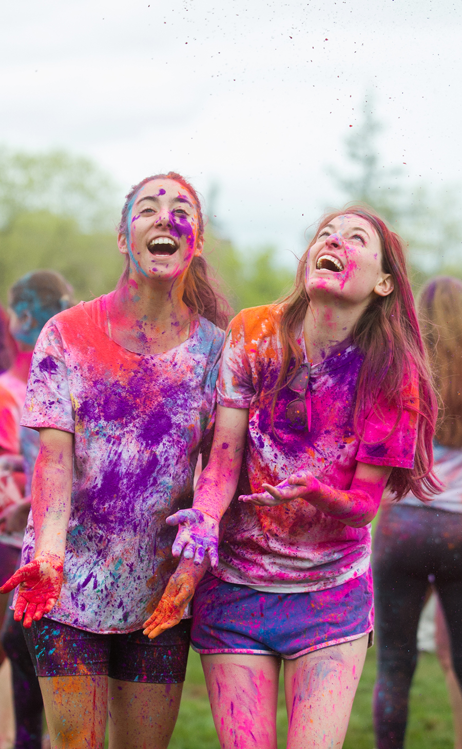 Two students smile from ear to ear, covered in brightly covered dyes at the Holi festival.
