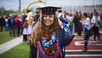 Sahara-Yvette Zamudio '17 in her commencement cap, gown, and colorful flowered leis on Crown field.