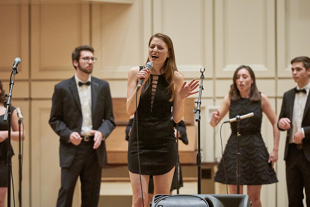A female student soloist at the mic leads the Resolutions on stage in Memorial Chapel