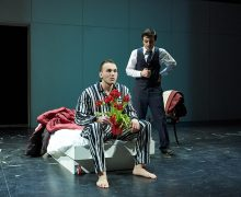A student actor in a suit on stage speaks with another actor in pajamas holding a vase of red flowers.