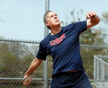 Roger Busch '63 in a USA shirt throwing a discus