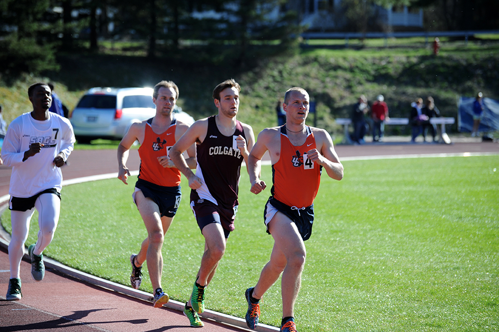 A Colgate men's track and field runner running against the competition on a track.