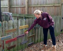 Brooke Baker Fox '93 standing next to signs of encouragement on her fence
