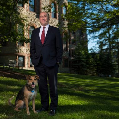 President Casey outside James B. Colgate Hall with his dog, Emrys.