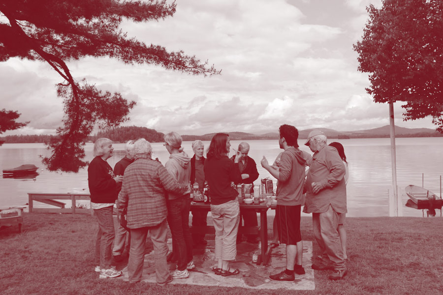 Adult campers share a snack on the lawn of Colgate Camp
