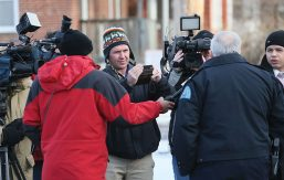 Reporter Joel Currier '00 records an outdoor interview with police