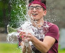 Water balloon breaks as student tries to catch it.