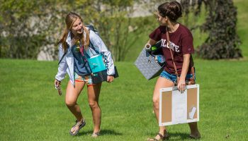 Two students carry items up the hill while chatting