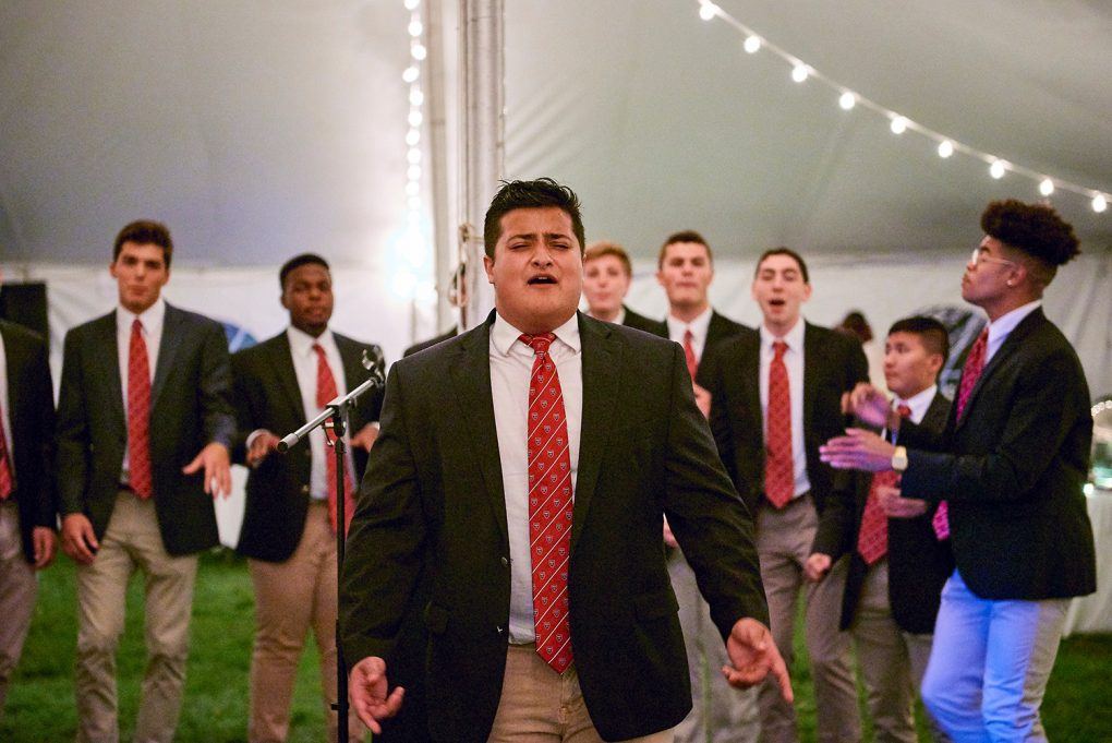 Student sings a solo with his a capella group under the lights in a tent