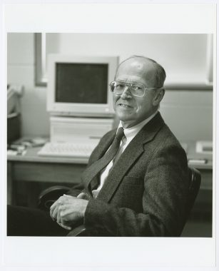 Black and white photo of James Howard Reynolds Jr. at a computer terminal