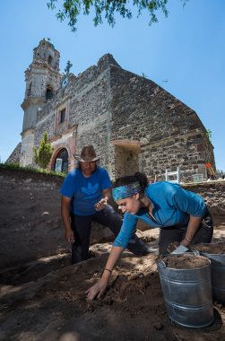 Student and local archaeologist work at the base of an old church wall