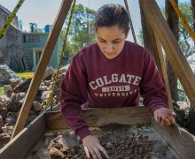 Female student in a Colgate sweatshirt uses a sifter in the field during research