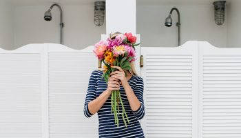 woman holding flower bouquet in front of her face