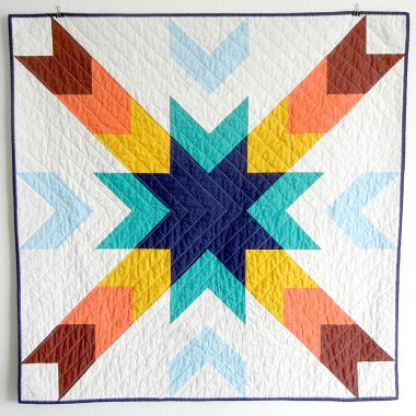 QLT quilt in blues, oranges, and yellow.