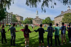 Students hold hands on the Academic Quad in an activity to get to know one another