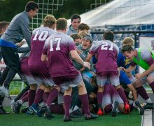 Men's soccer team celebrates on the field