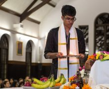 Student lighting candle for Diwali