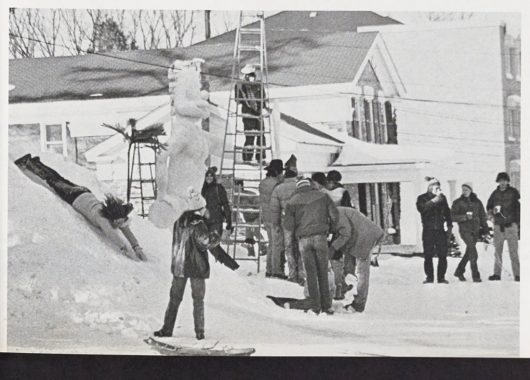 Black and white photo of students building snow sculptures and sliding in the snow