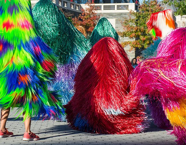 Students dancing in colorful soundsuits