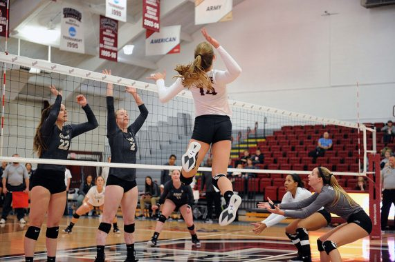Colgate volleyball player jumps for spike