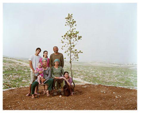 Family posing with sapling