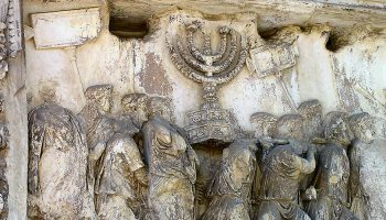 Stone relief of people carrying menorah