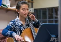 Smiling student playing cello