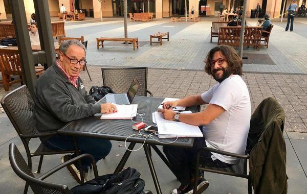 Costa and classmate at table on cafe patio