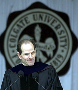 Eliot Spitzer at the commencement podium with the Colgate seal in the background