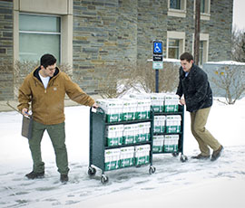 Cameron Borriello '14 and Michael Hendricks '14, two of four new co-owners of EcoCampus, deliver paper recently to Case Library.