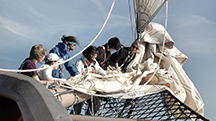 Leah Feldman '14 (third from left) and her shipmates furling the topsail on the Corwith Cramer (Courtesy of the Williams-Mystic Maritime Studies Program