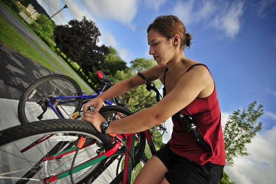 Chelsea Hoffman '11, unlocks one of the Green Bicycles outside of the Case Geyer Library on the Colgate Campus.