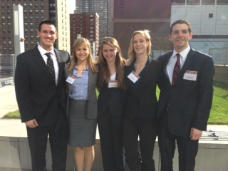 Students pose for a group shot in business attire.