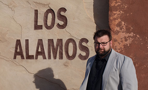 Professor Jason Keith stands in front of the entrance to Los Alamos National Laboratory