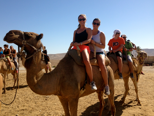 Madison Grant '16 (front) rides a camel in Israel.
