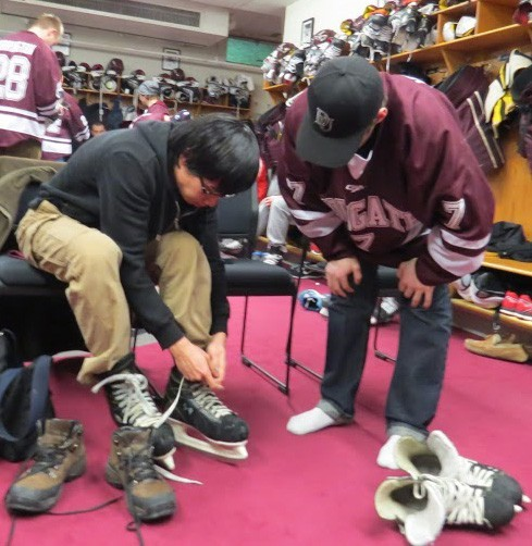 Ryan Johnston helps a Colgate student put his skates on prior to hitting the ice.