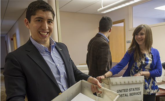 Members of the Colgate Office of Admission carry loads of acceptance letters to the mailroom for delivery Tuesday. (Photo by Duy Trinh)