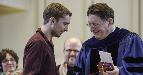 Evan Chartier '14 accepts the 1819 Award from President Herbst at the Senior Awards Convocation Ceremony. (Photo by Duy Trinh '14)